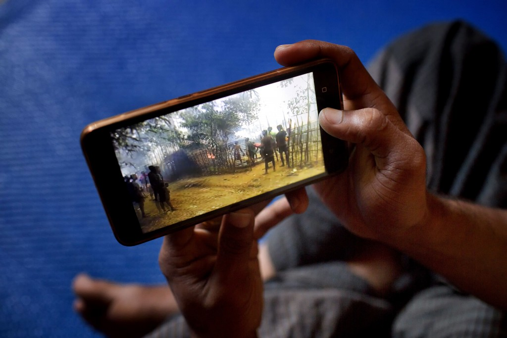 In this Dec. 23, 2017 photo, Mujibullah, 22, a Rohingya refugee watches a video, which he has shot in Myanmar before crossing over into Bangladesh, at...