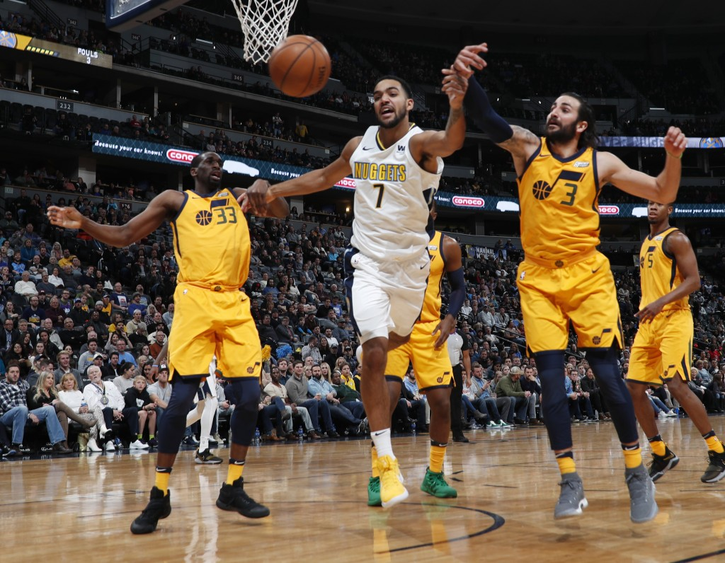 Denver Nuggets forward Trey Lyles, center, battles for control of a rebound with Utah Jazz center Ekpe Udoh, left, and guard Ricky Rubio, of Spain, in...