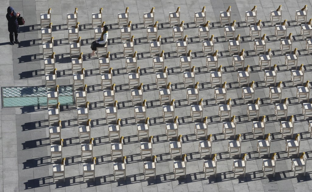 In this Dec. 27, 2017, file photo, a woman takes a photo in front of the comfort woman statue and empty chairs symbolizing victims of comfort women in...