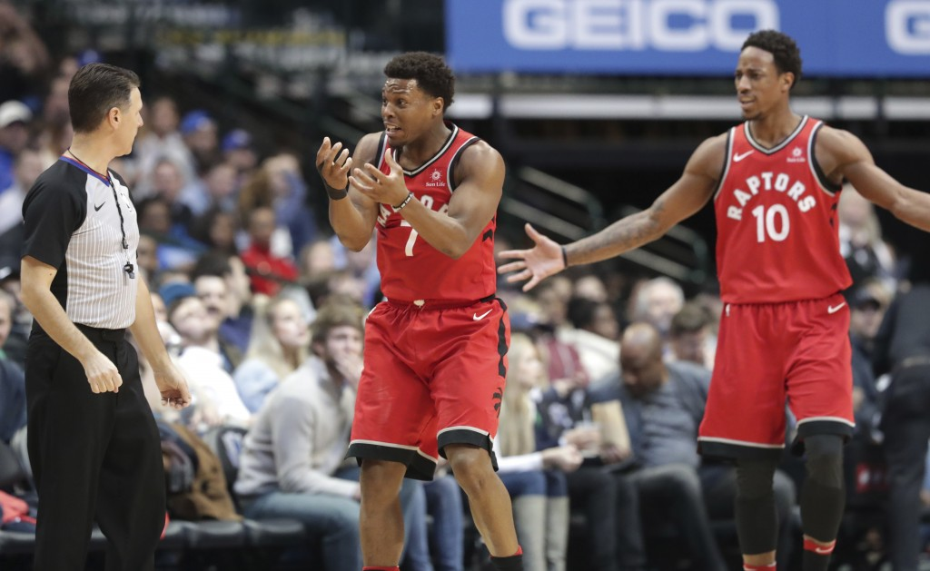 Toronto Raptors guards Kyle Lowry (7) and DeMar DeRozan (10) question a call during the second half of an NBA basketball game against the Dallas Maver...
