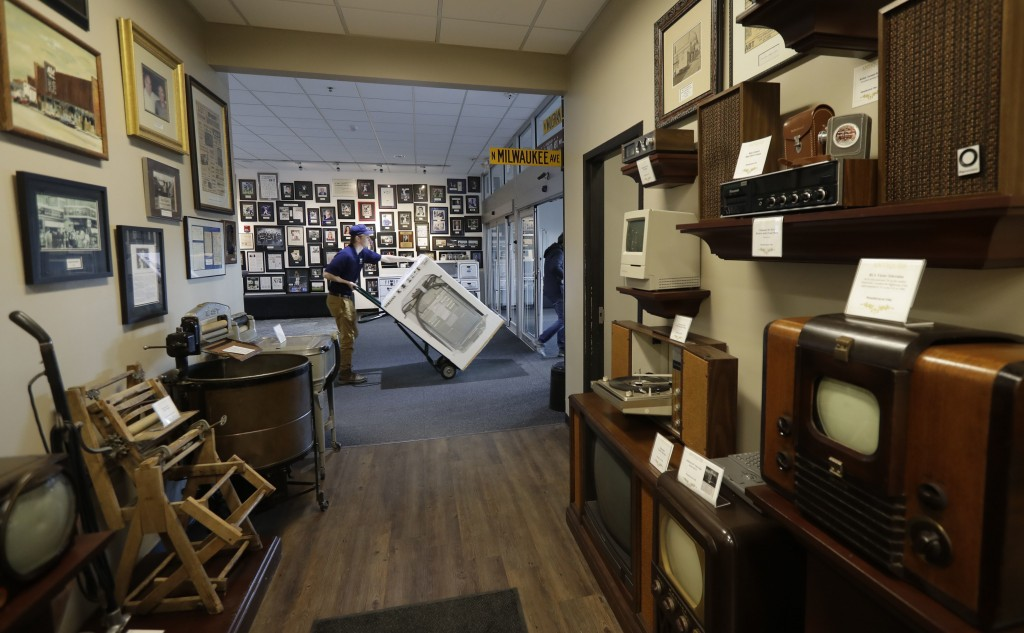 In this Wednesday, Dec. 20, 2017, photo, another appliance purchased at the Abt Electronics store is wheeled out past a gallery of antique and early e...