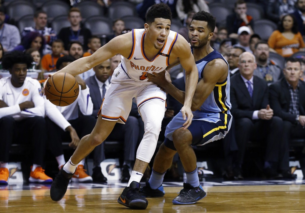 Back from injury, Phoenix Suns guard Devin Booker (1) dribbles past Memphis Grizzlies guard Andrew Harrison, right, during the first half of an NBA ba...
