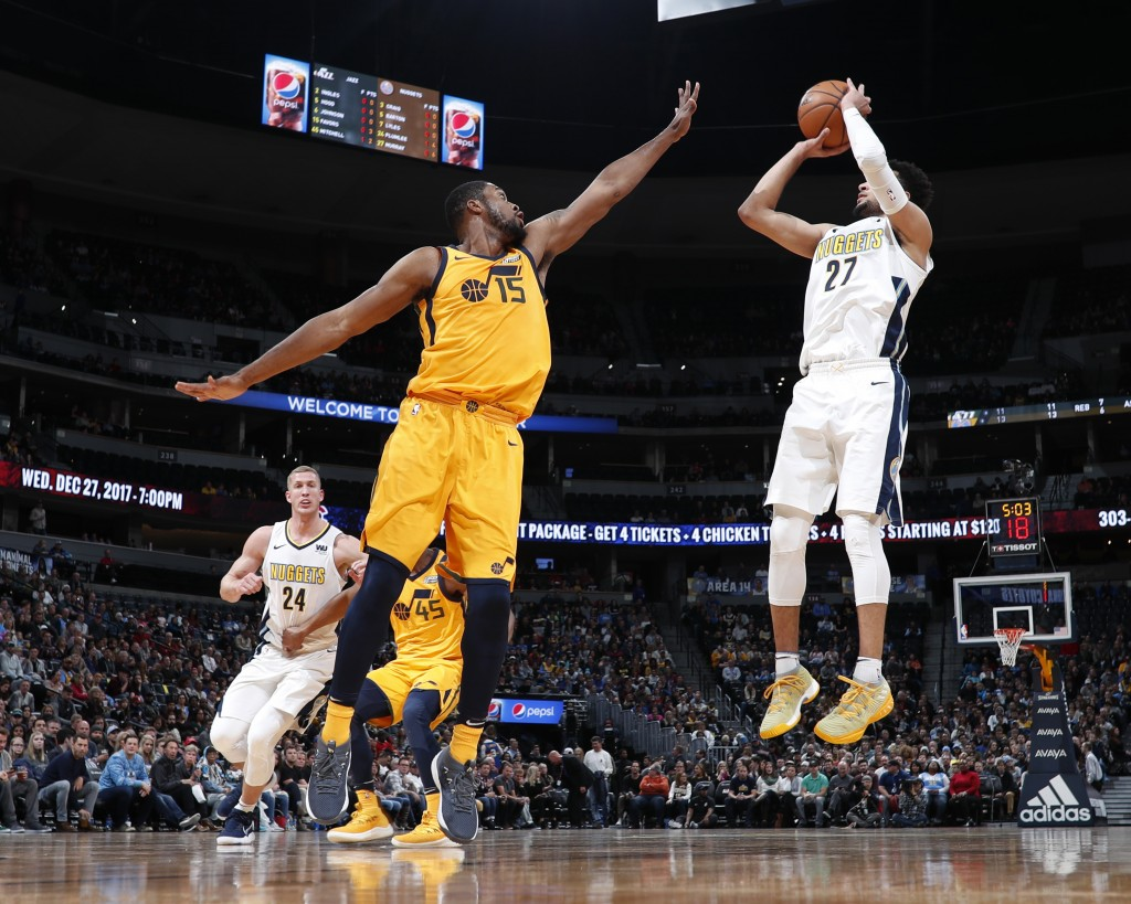 Utah Jazz forward Derrick Favors, left, reaches up to block a shot by Denver Nuggets guard Jamal Murray in the first half of an NBA basketball game, T...