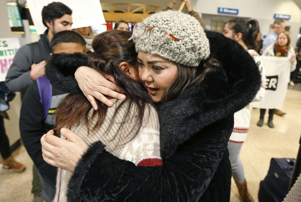 In this Monday, Dec. 25, 2017, photo, Maria Santiago Garcia, left, receives a hug before going through security gate at the Salt Lake City Internation...