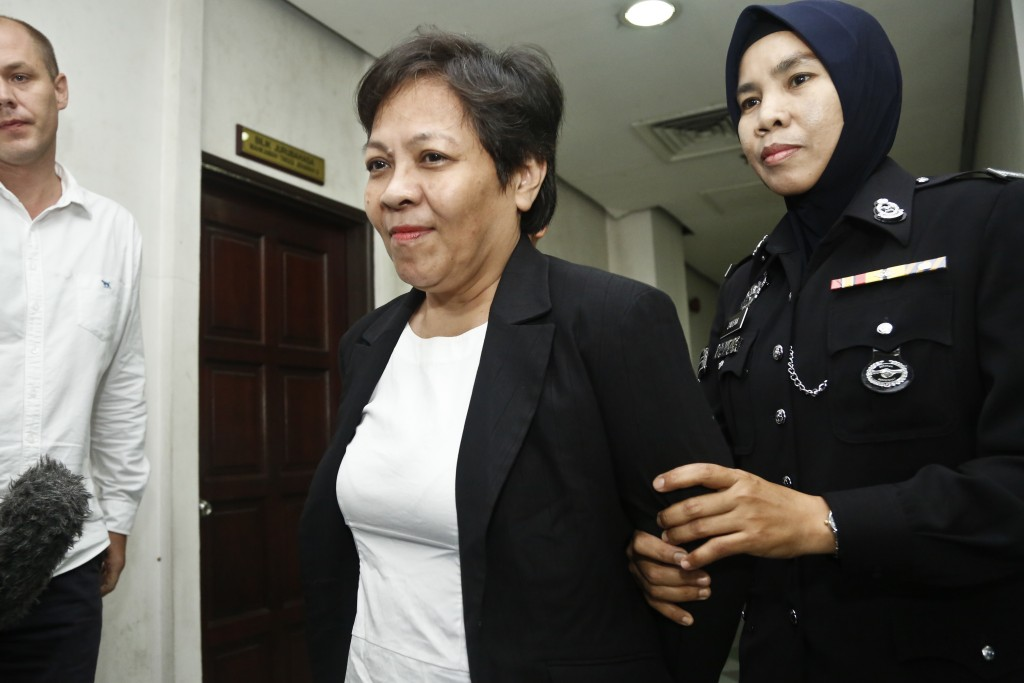 Australian Maria Elvira Pinto Exposto, center, is escorted by a police officer during a court hearing at Shah Alam High Court in Shah Alam, Malaysia, ...