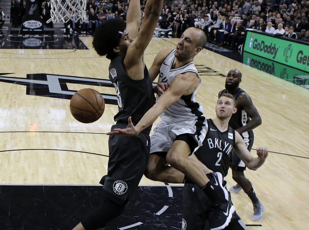 San Antonio Spurs guard Manu Ginobili, center, drives to the basket past Brooklyn Nets center Jarrett Allen, left, during the first half of an NBA bas...