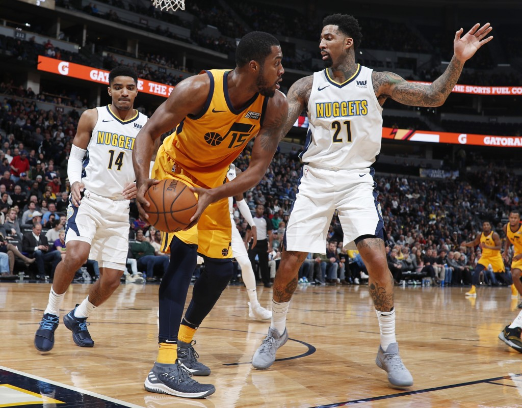 Utah Jazz forward Derrick Favors, center, pulls in a loose ball as Denver Nuggets guard Gary Harris, left, and forward Wilson Chandler defend in the s...