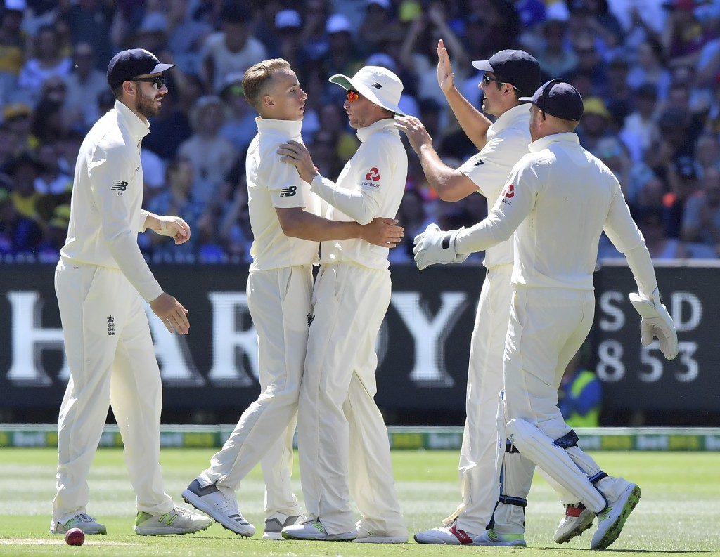 England's Tom Curran, second left, is congratulated by teammates after taking the wicket of Australia's Steve Smith during the second day of their Ash...