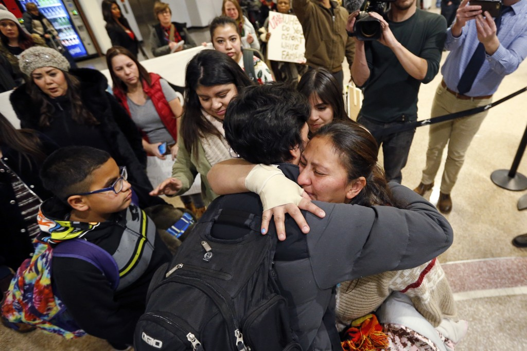 In this Monday, Dec. 25, 2017 photo, Maria Santiago Garcia, right, receives a hug before going through security gate at the Salt Lake City Internation...