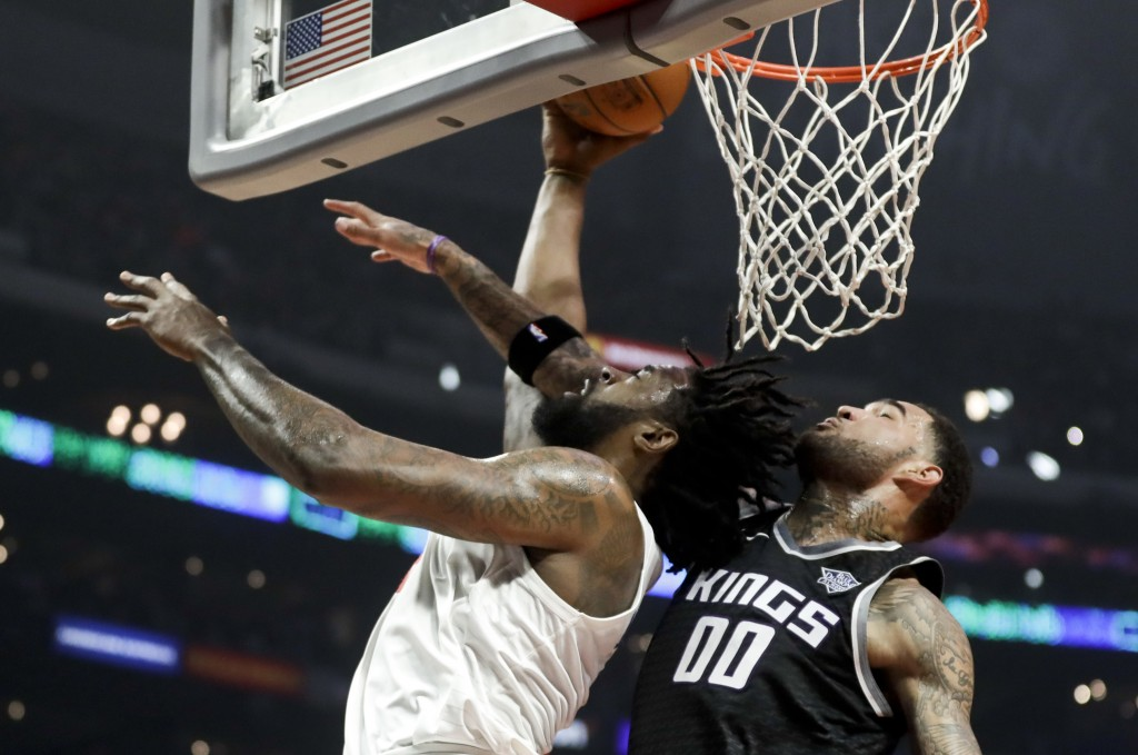 LA Clippers center DeAndre Jordan, shoots past Sacramento Kings center Willie Cauley-Stein during the first half of an NBA basketball game in Los Ange...