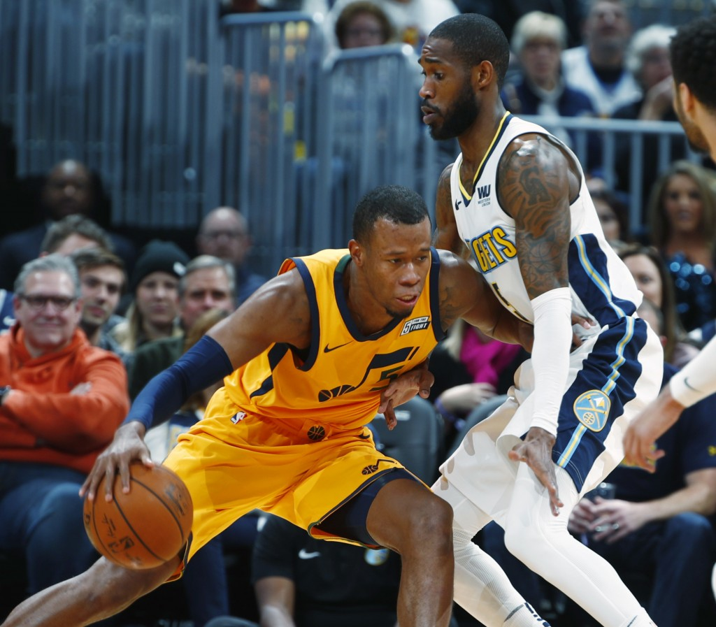 Utah Jazz guard Rodney Hood, left, works the ball inside as Denver Nuggets guard Will Barton defends in the first half of an NBA basketball game, Tues...