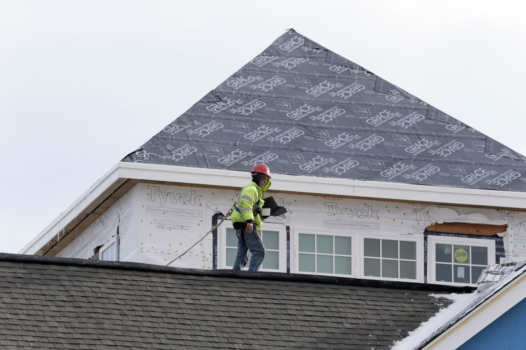 FILE - In this Tuesday, Jan. 19, 2016, file photo, a roofing construction contractor works on a new housing condominium project in Gloucester, Mass. H...