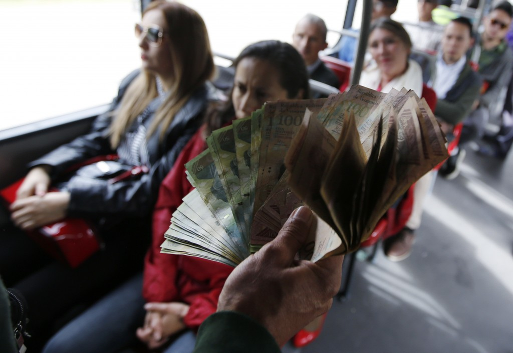 In this Dec. 12, 2017 photo, Venezuelan national Jorge Gutierrez holds a wad of worthless Venezuelan currency as he rides a public bus in Bogota, Colo...
