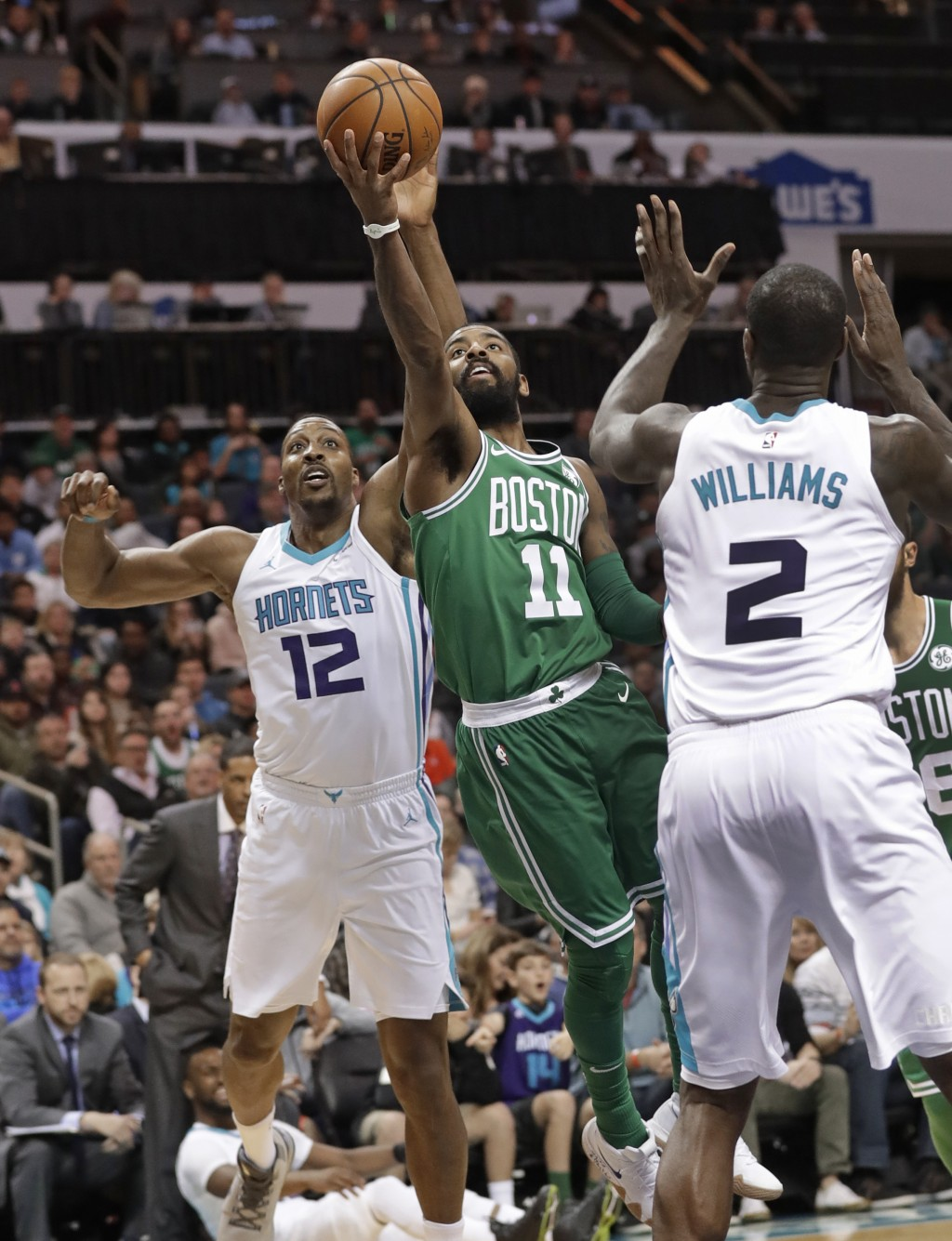 Boston Celtics' Kyrie Irving (11) drives between Charlotte Hornets' Dwight Howard (12) and Marvin Williams (2) during the first half of an NBA basketb...