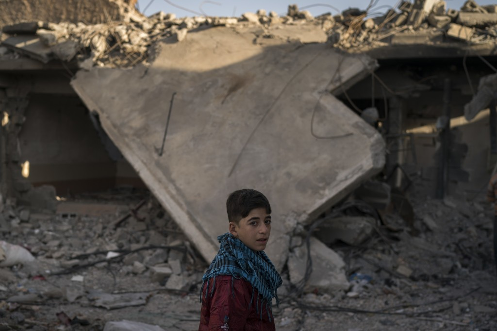 In this Nov. 16, 2017 photo, a boy who recently returned to the Old City walks past a destroyed building near his house in Mosul, Iraq. The U.N. estim...