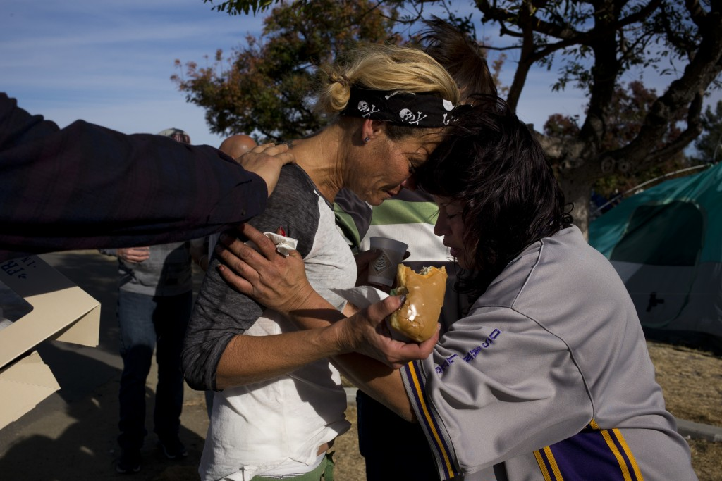 Amy Potter, left, and Victoria Pena, who are both homeless, pray for each other while holding donuts and coffee donated by local church members in a h...