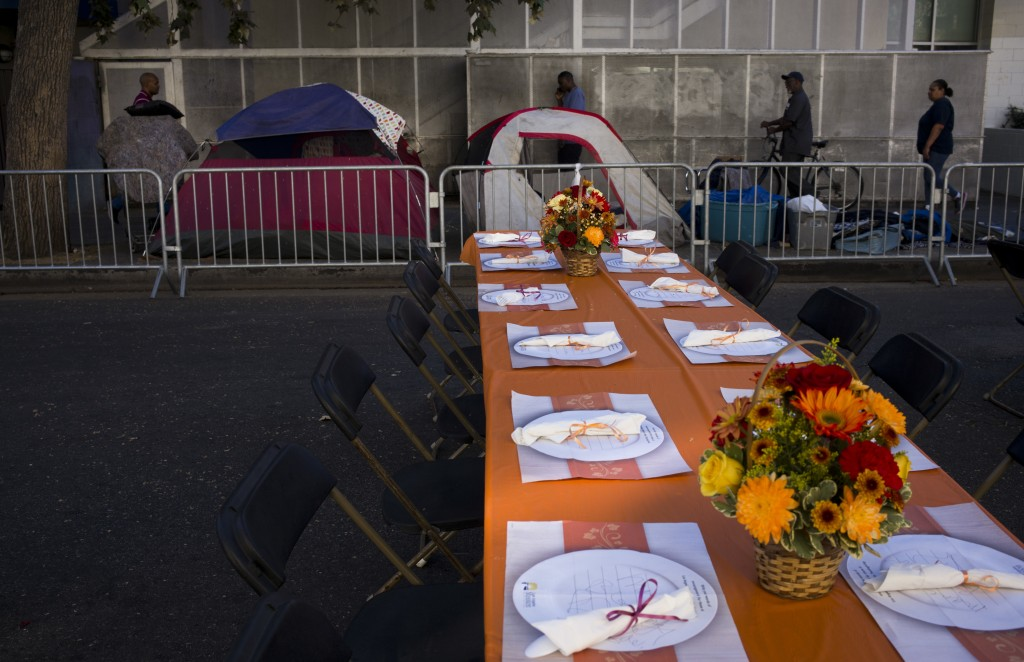Homeless tents are pitched on a sidewalk in the Skid Row area of downtown Los Angeles Wednesday, Nov. 22, 2017, as tables are set up on the street to ...