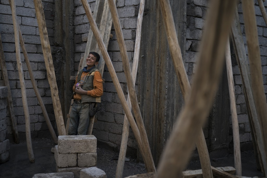 In this Nov. 14, 2017 photo, a young construction worker smiles during a break as he rebuilds a destroyed shop in the Old City of Mosul, Iraq. The U.N...