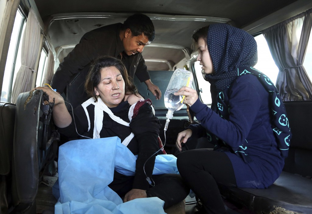 People assist an injured woman following a suicide attack in Kabul, Afghanistan, Thursday, Dec. 28, 2017. Authorities say two simultaneous attacks in ...