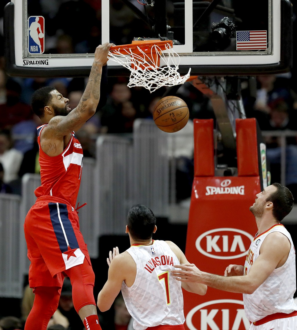 Washington Wizards' Markieff Morris, left, dunks in front of Atlanta Hawks' Ersan Ilyasova, of Turkey, and Miles Plumlee, right, in the first quarter ...