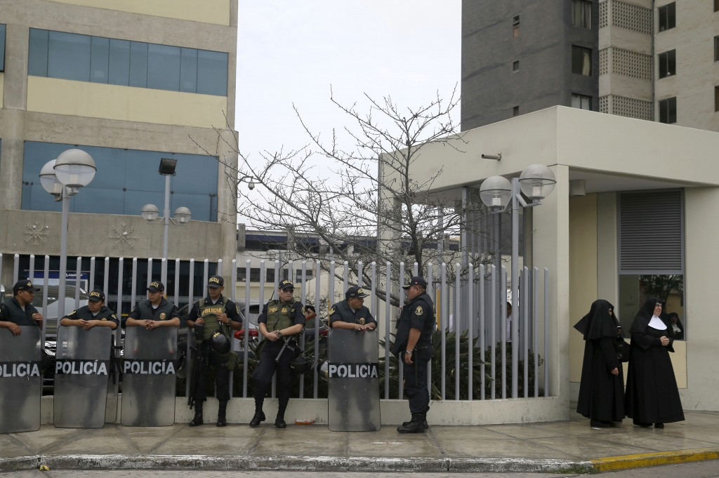 Nuns stands next to a group of police who are standing guard outside the clinic where former President Alberto Fujimori was admitted, in Lima, Peru, W...