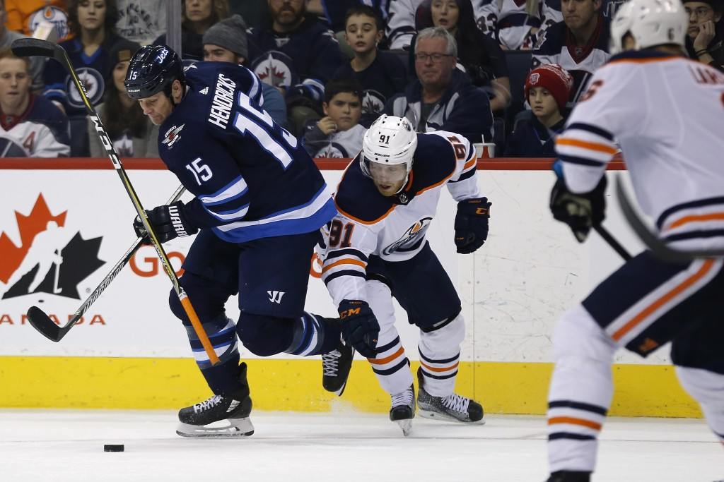 Winnipeg Jets' Matt Hendricks (15) gets around Edmonton Oilers' Drake Caggiula (91) during the second period of an NHL hockey game Wednesday, Dec. 27,...
