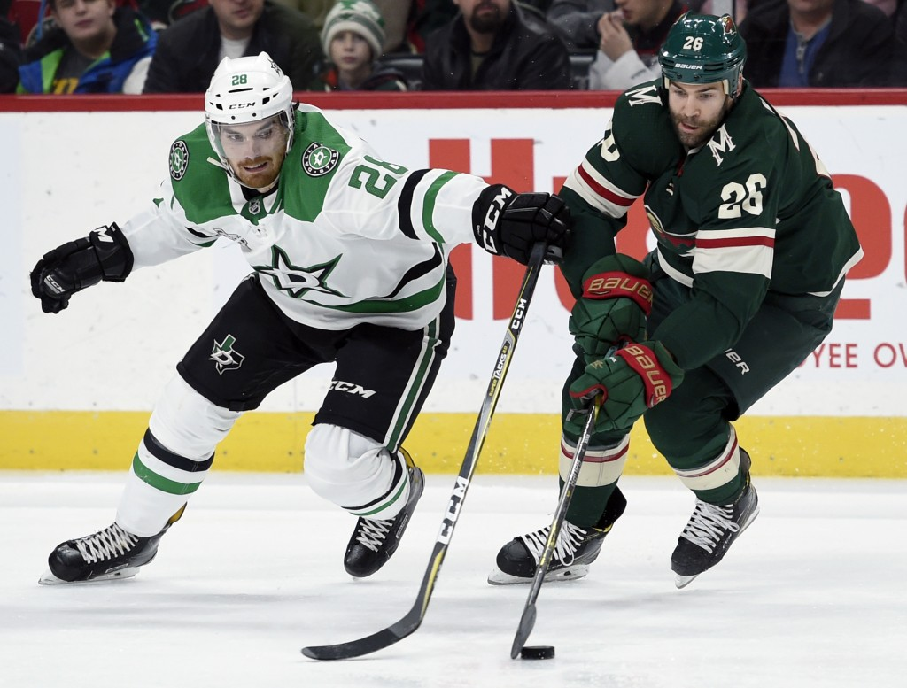 Minnesota Wild's Daniel Winnik (26) moves the puck next to Dallas Stars' Stephen Johns (28) during the second period of an NHL hockey game Wednesday, ...
