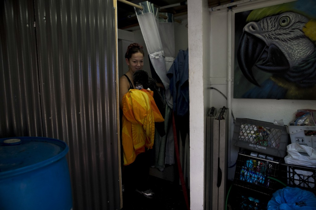 Homeless Kimberly Gardea, 35, walks out of a shower stall inside a trailer built to provide showers to homeless people living on the Santa Ana River t...