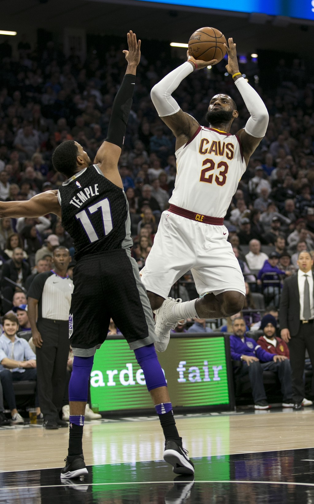 Cleveland Cavaliers forward LeBron James, right, shoots over Sacramento Kings guard Garrett Temple during the first quarter of an NBA basketball game,...