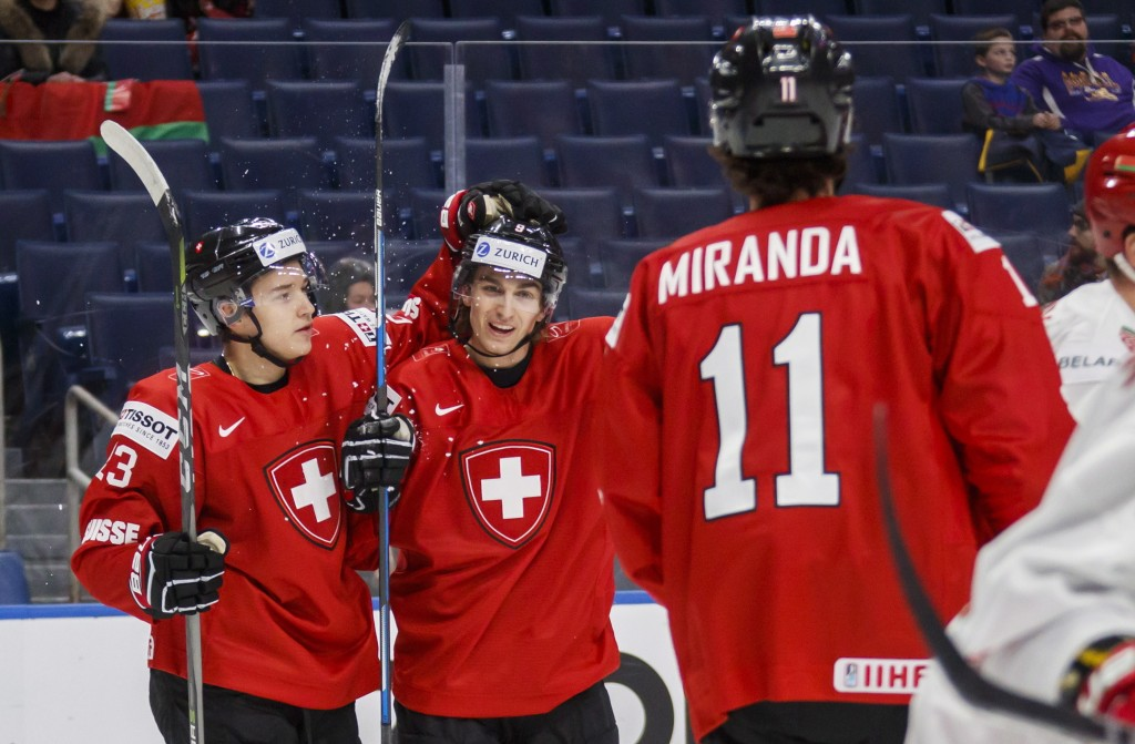Switzerland's Nicolas Muller, center, celebrates his goal with teammates Philipp Kurashev, left, and Marco Miranda against Belarus during the first pe...