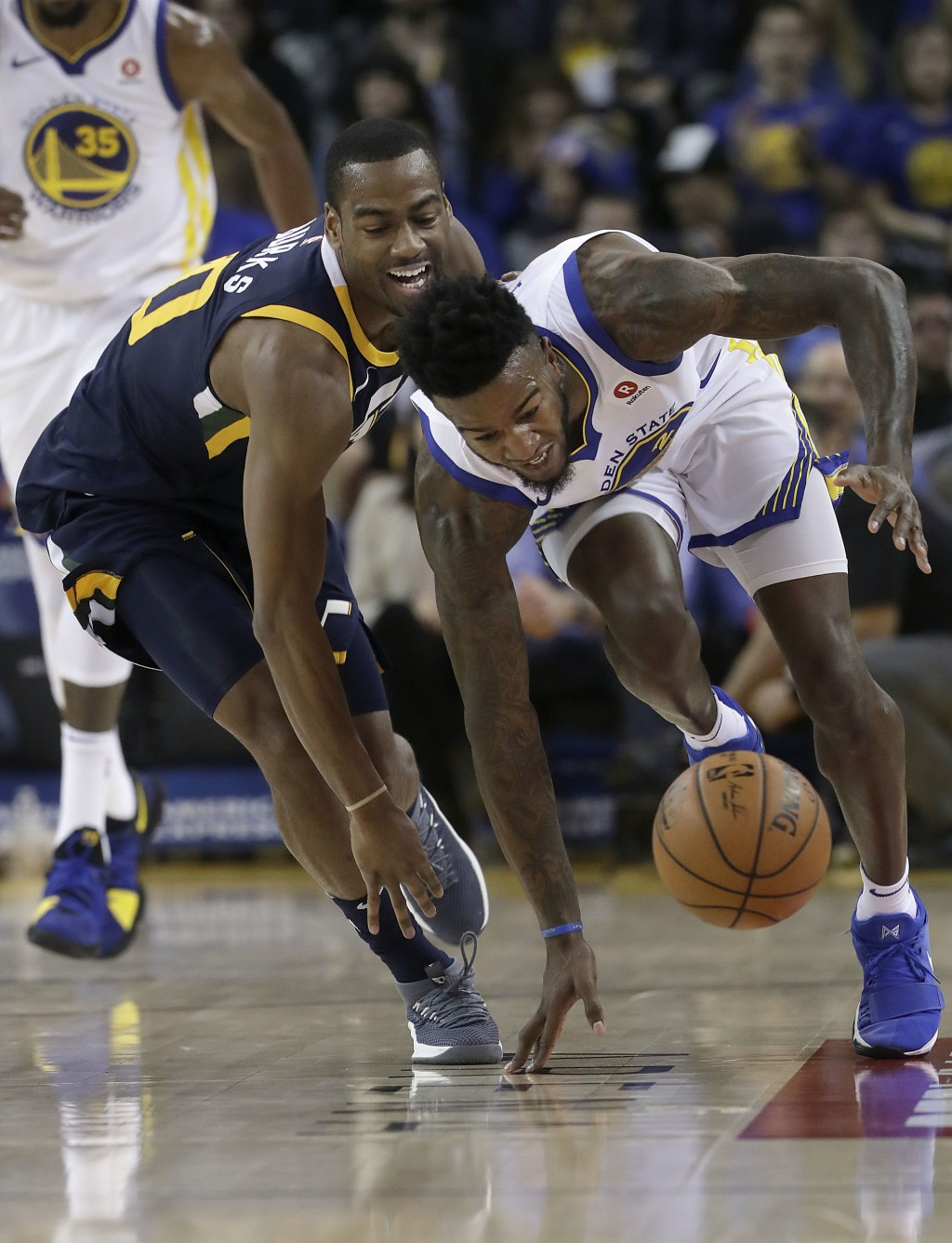 Golden State Warriors forward Jordan Bell, right, chases a loose ball next to Utah Jazz guard Alec Burks during the first half of an NBA basketball ga...