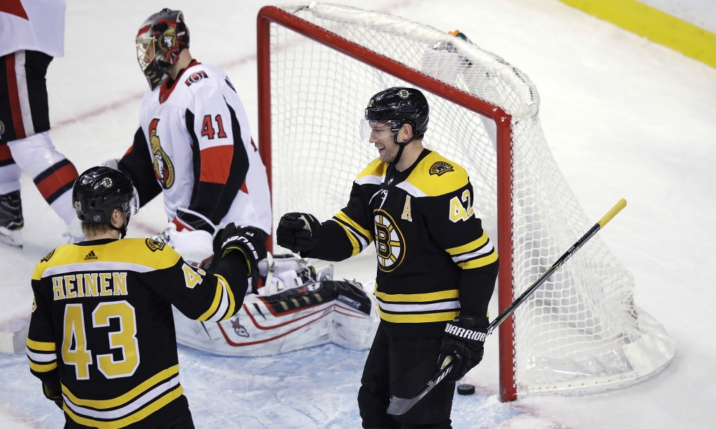 Boston Bruins right wing David Backes (42) is congratulated by Danton Heinen (43) after his goal off Ottawa Senators goalie Craig Anderson (41) during...