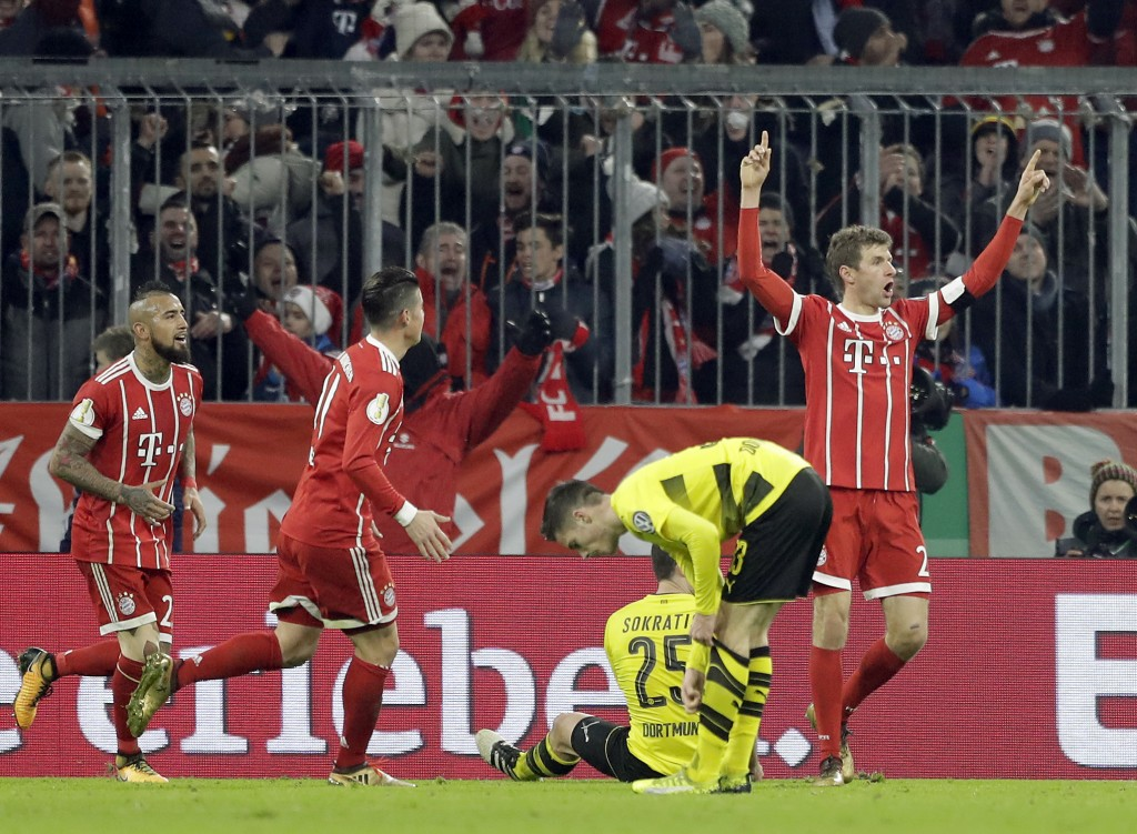FILE - In this Dec. 20, 2017 file photo Bayern's Thomas Mueller, right, celebrates after scoring his side's 2nd goal during the round of sixteen Germa...
