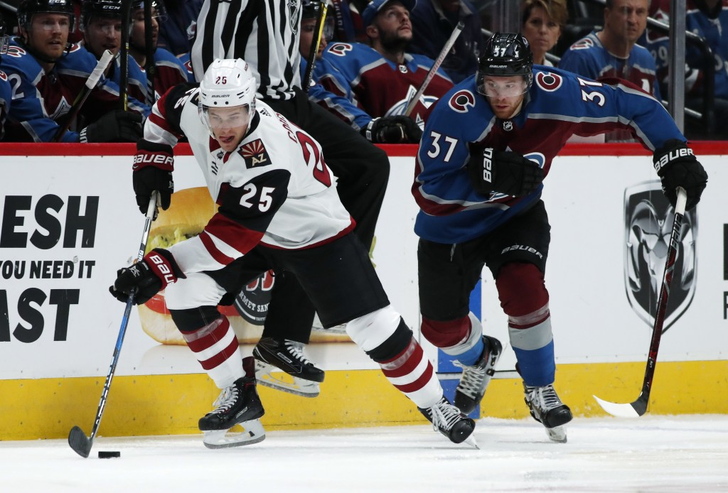 Arizona Coyotes center Nick Cousins, left, races downice with the puck past Colorado Avalanche left wing J.T. Compher in the second period of an NHL h...