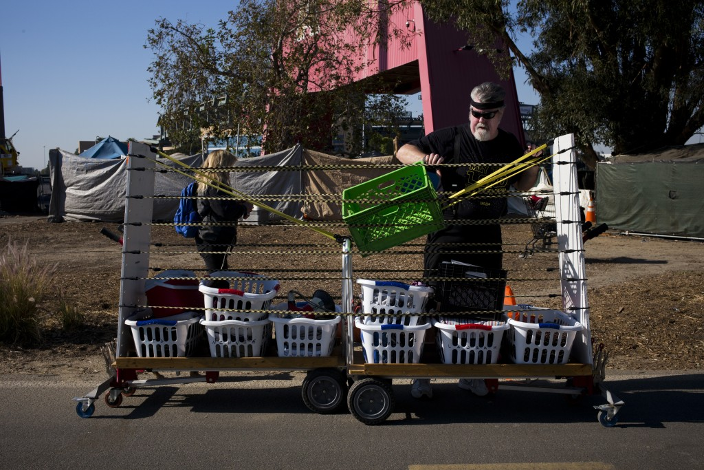 Joel Sheehan, who does free laundry for homeless people living on the Santa Ana River trail, delivers washed clothes in baskets, each labeled with an ...