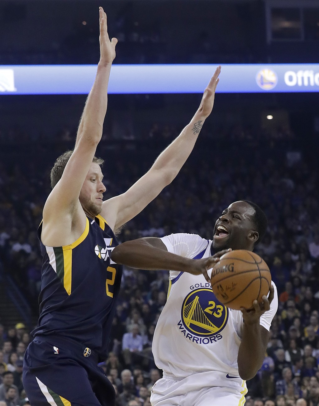 Golden State Warriors forward Draymond Green (23) is defended by Utah Jazz forward Joe Ingles during the first half of an NBA basketball game in Oakla...