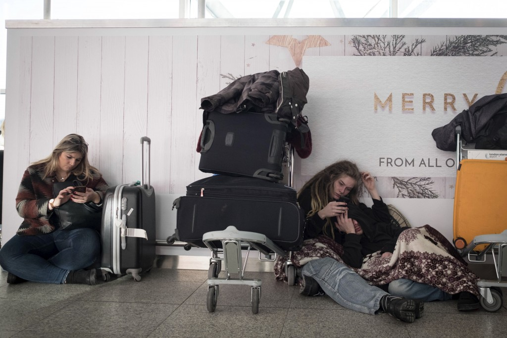 Passengers sit in Stansted Airport terminal, Thursday Dec. 28, 2017, where some passengers were stranded overnight after flights were cancelled due to...