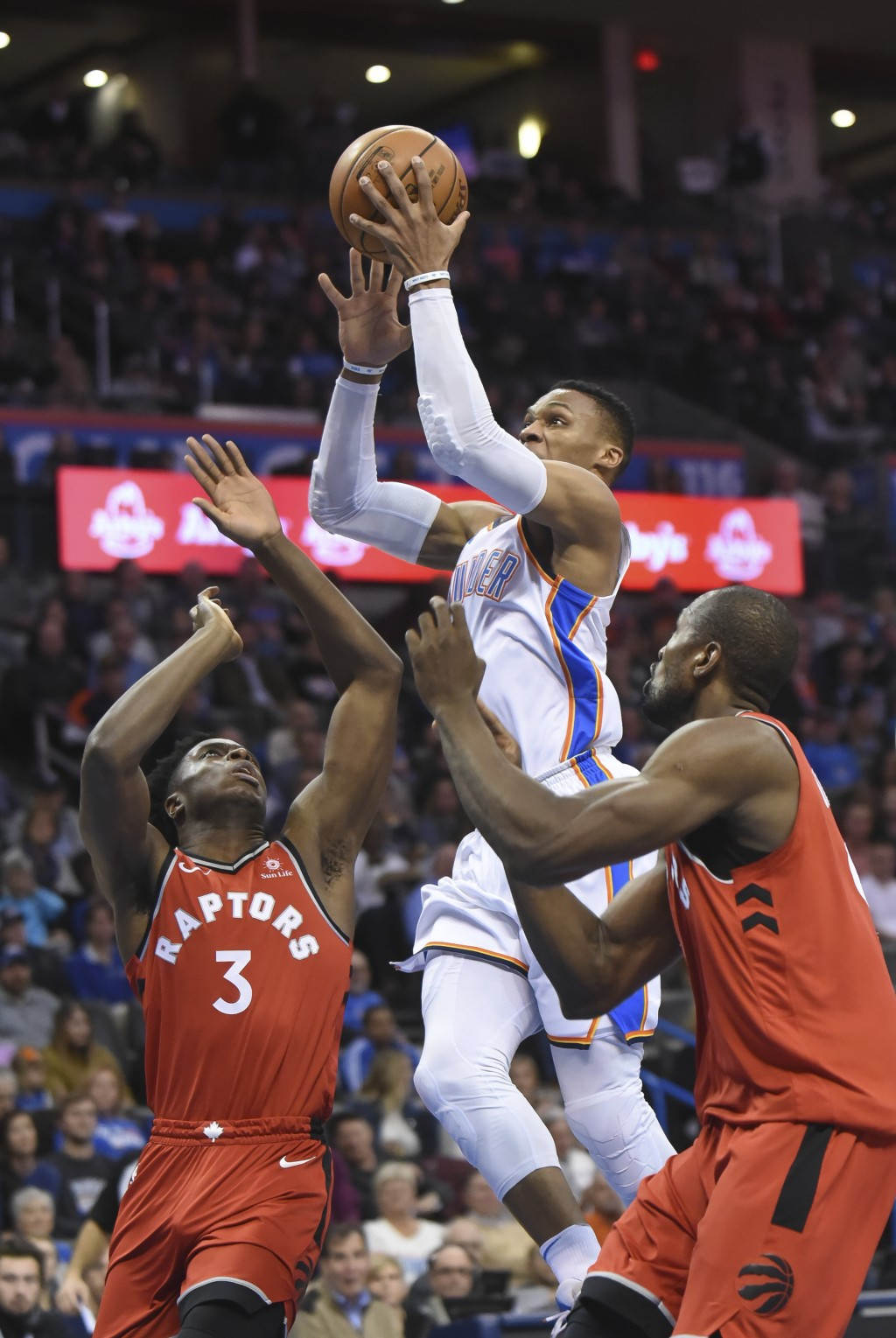 Oklahoma City Thunder's Russell Westbrook (0) goes up for a shot over Toronto Raptors' OG Anunoby (3) and Serge Ibaka (9) during the second half of an...