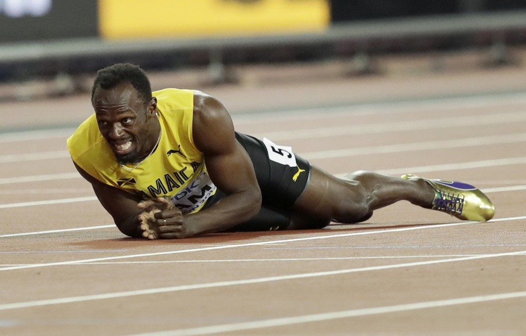 FILE - In this Aug. 12, 2017, file photo, Jamaica's Usain Bolt lies on the track after he injured himself in the 4x100 meter relay final at the World ...