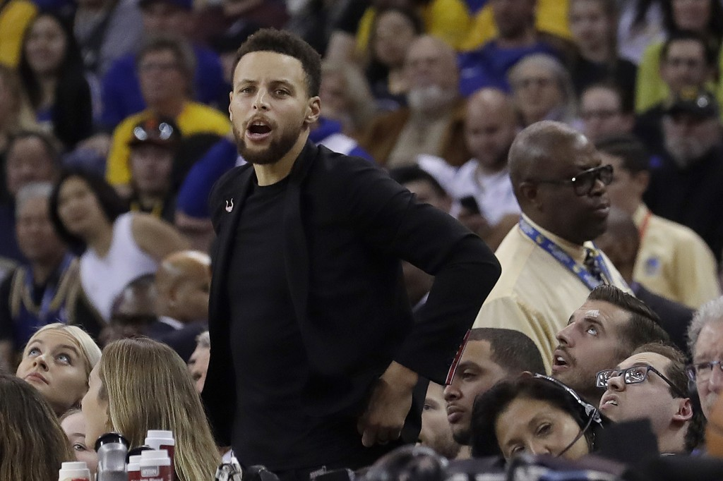 Injured Golden State Warriors guard Stephen Curry watches from the bench during the first half of the team's NBA basketball game against the Utah Jazz...