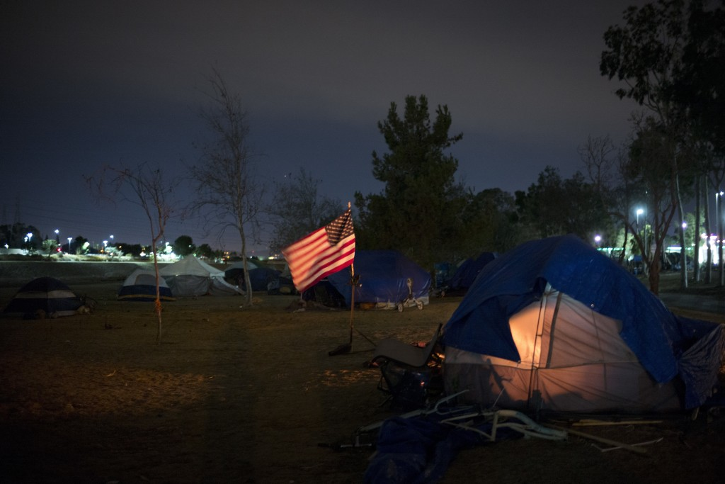 Homeless tents are pitched around an America flag along the Santa Ana River trail Sunday, Dec. 10, 2017, in Anaheim, Calif. Advocates say the homeless...