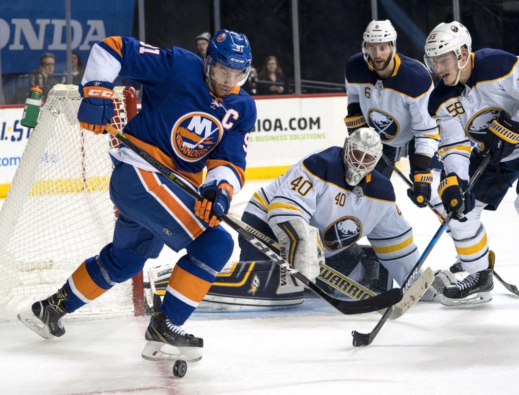 New York Islanders' John Tavares goes for the puck as Buffalo Sabres' Rasmus Ristolainen (55), Marco Scandella (6) and goalie Robin Lehner look on dur...