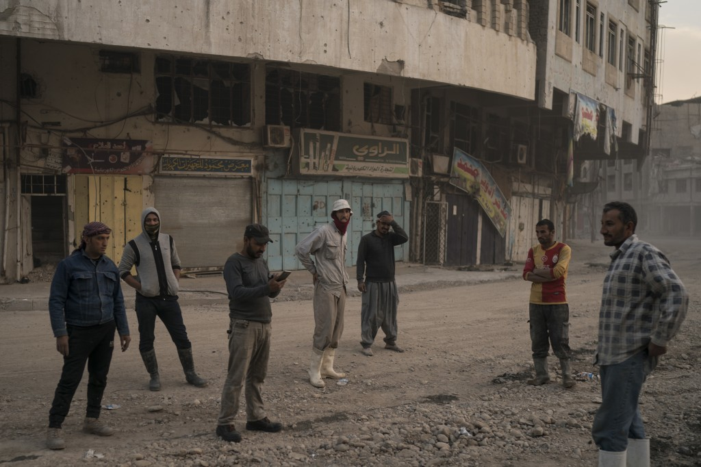 In this Nov. 15, 2017 photo, construction workers gather on a commercial street in the Old City of Mosul, Iraq. The scope of destruction in the neighb...