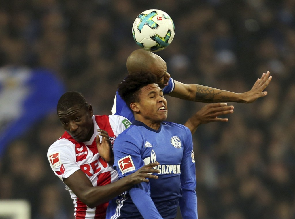 FILE - In this Dec. 2, 2017 file photo Schalke's Naldo, top, and Weston McKennie, right, battle for the ball with Sehrou Guirassy of Cologne during th...