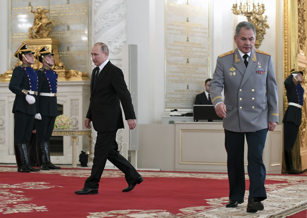 Russian President Vladimir Putin, left, and Russian Defence Minister Sergei Shoigu, right, arrive for an award ceremony in the Kremlin, in Moscow, Rus...