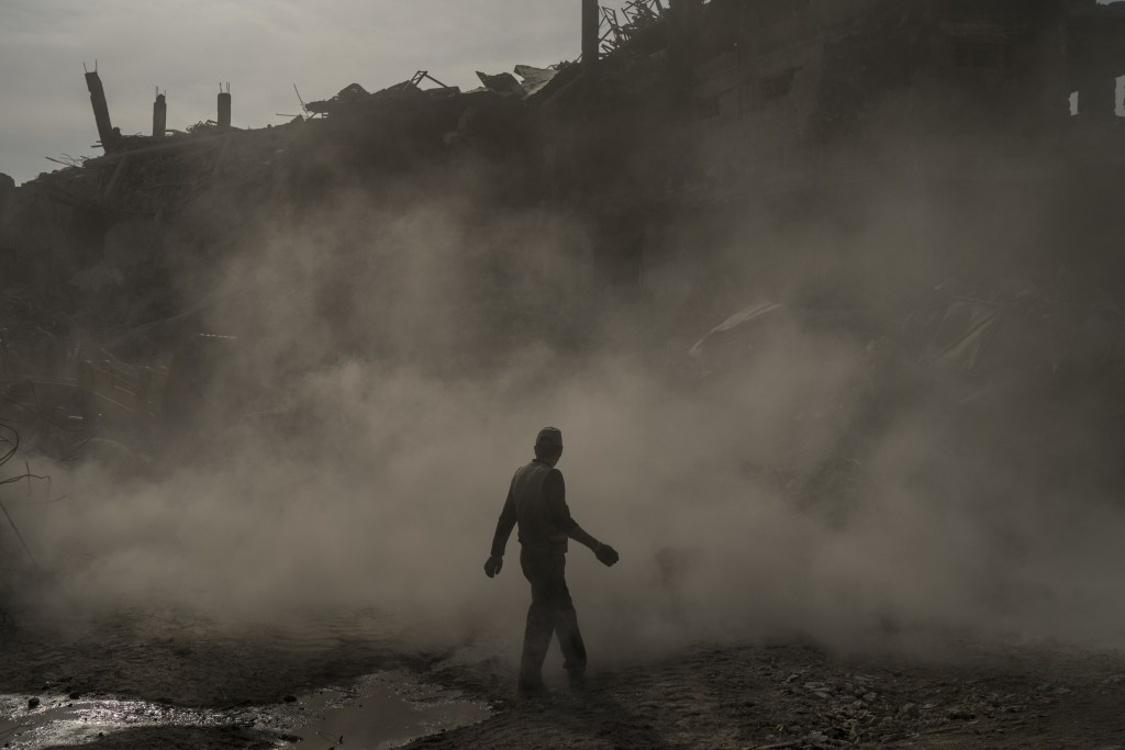 In this Nov. 18, 2017 photo, a construction worker walks amid a cloud of dust as a bulldozer remove debris from destroyed shops in the Old City of Mos...