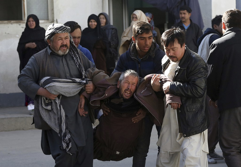 A distraught man is carried following a suicide attack in Kabul, Afghanistan, Thursday, Dec. 28, 2017. Authorities say attackers stormed the Shiite Mu...