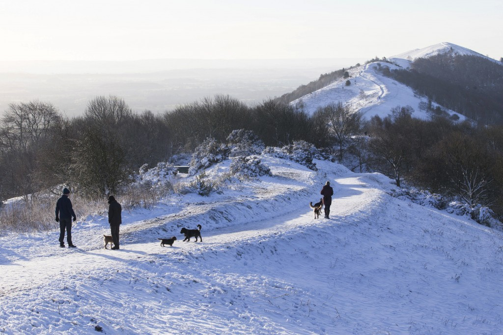 People walk their dogs in the snow covered Malvern Hills, Malvern, east England, Thursday Dec. 28, 2017, as plunging temperatures and widespread ice a...
