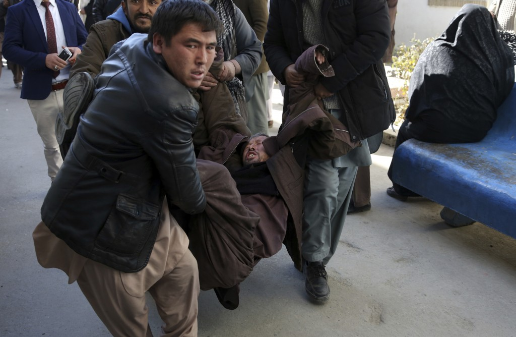 A man is carried into a hospital in tears after a suicide attack in Kabul, Afghanistan, Thursday, Dec. 28, 2017. Authorities say two simultaneous atta...