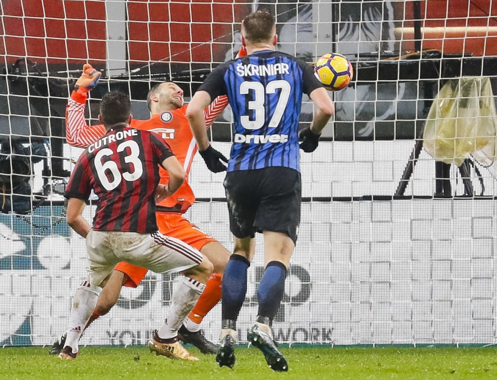 AC Milan's Patrick Cutrone, left, scores for his team during an Italian Cup quarter-final soccer match between Milan and Inter Milan at the San Siro s...